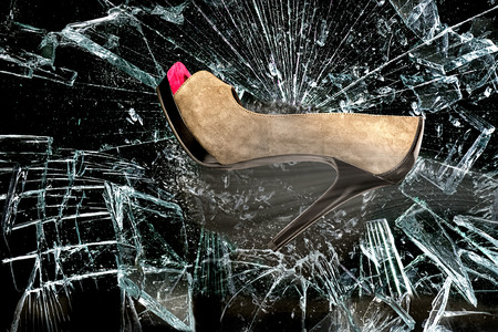 High heel shoe through broken glass window.