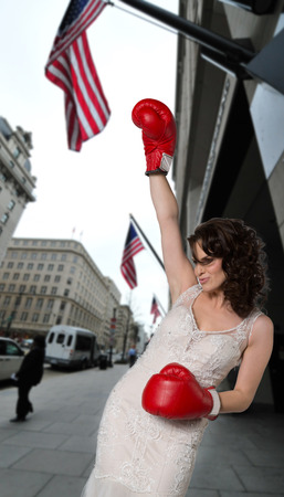 Boxing beauty on city street showing a winning pose. photo