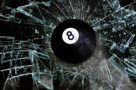 billiard balls: Eight ball going through broken glass. Stock Photo