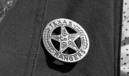 lawman: Old Texas ranger cowboy badge in black and white.