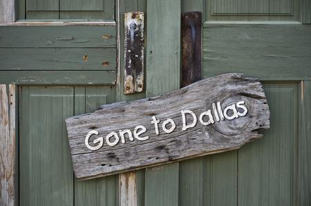 green door: Gone to Dallas sign on old green door.