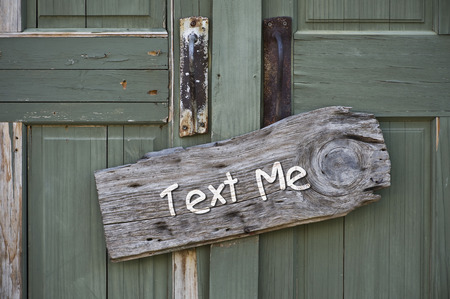 old sign: Text me sign on old green door.