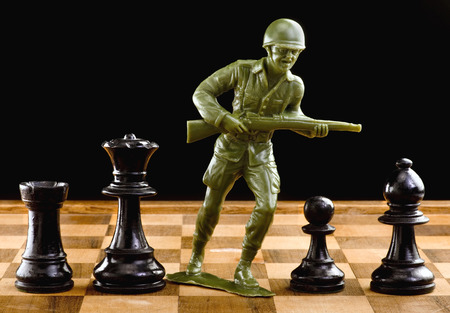 plastic soldier: Chessmen with green toy soldier taking on to battle.