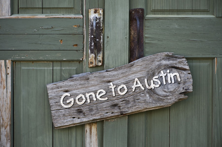 unavailable: Gone to Austin,Texas sign on old green doors. Stock Photo