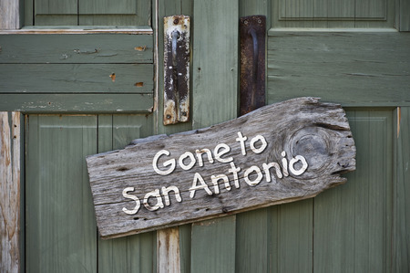 gone: Gone to San Antonio,Texas sign on old green door. Stock Photo