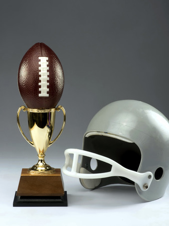 face guard: Youth football with winning trophy and helmet. Stock Photo