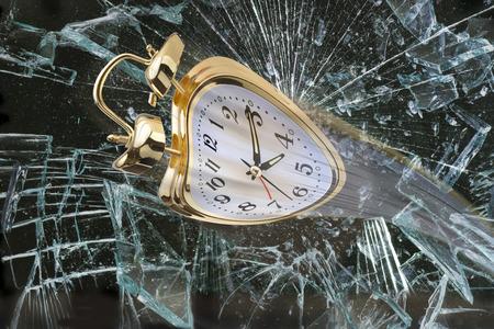 Alarm clock flying through broken window.