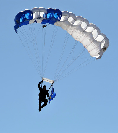 Parachutist in the deep blue sky.