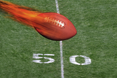 fierce competition: Football on fire crossing the fifty yard line.. Stock Photo