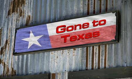 gone: Old gone to Texas sign on tin barn. Stock Photo