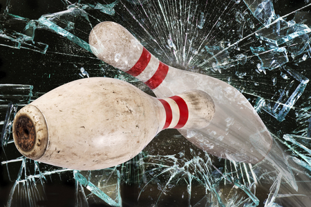bowling strike: Bowling pin shattering a glass window.