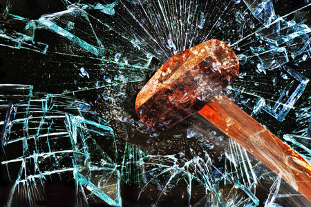 Iron hammer breaking glass window. Stock Photo