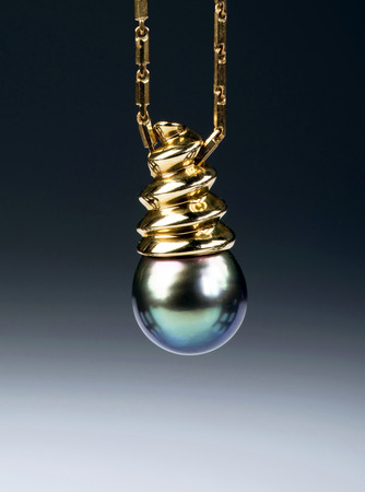pearl necklace: Black Tahitian pearl mounted in gold with room for your type.