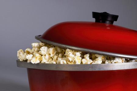 Palomitas de maíz de la manera pasada de moda en una olla de hierro rojo.