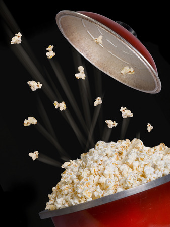 bowl of popcorn: Popcorn flying and exploding from red kettle.