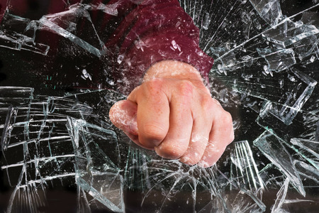 Hand door glazen raam gebroken.