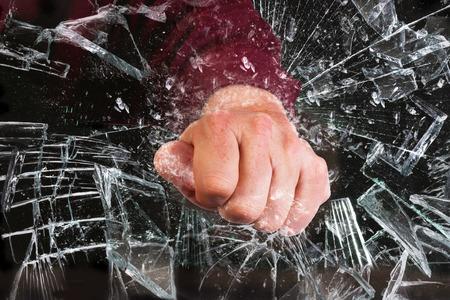 Hand through broken glass window.