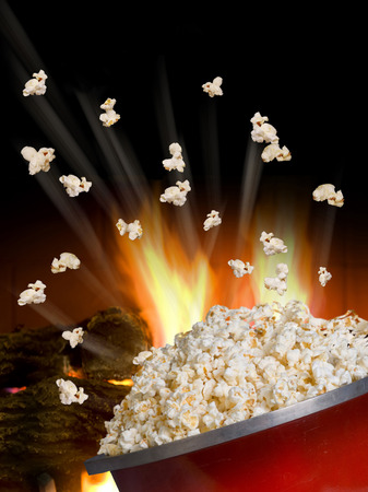 comfort food: Popcorn flying and exploding from red kettle.