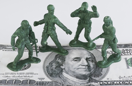 green military miniature: Guarding American money with green toy soldiers.