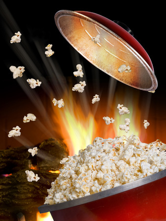 popcorn bowls: Popping popcorn the old fashion way in a red iron pot.