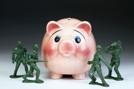 debt: Protecting American money in the piggy bank with green toy soldiers.