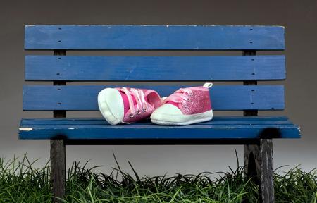 ni�as peque�as: Zapatitos rosados ??lindos en el banco del parque azul. Foto de archivo