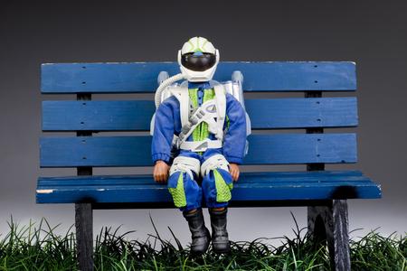 spacesuit: Rocket man on a blue park bench.