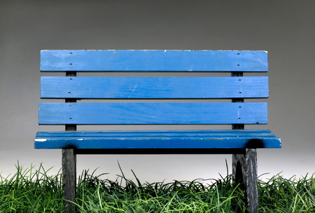 Old blue park bench on green grass.