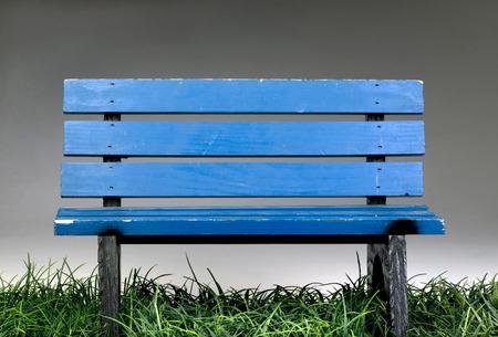 Oude blauwe bankje op groen gras. Stockfoto