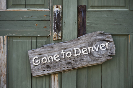 unavailable: Gone to Denver sign on old green doors.