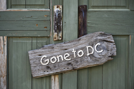 congressional: Gone to Washington DC sign on old green doors.
