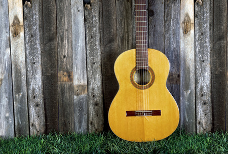 acoustical: Classical guitar against old fence with room for your type. Stock Photo