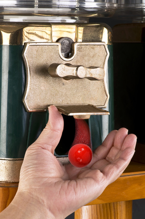 gumball: Gumball machine dropping red gumball. Stock Photo