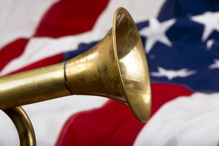 bugle: Brass bugle on a American flag .