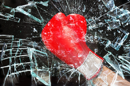 Boxing glove through broken glass window.