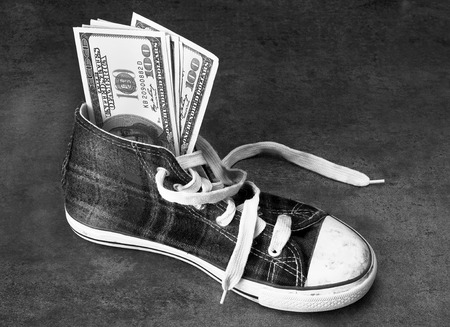 Kids shoe stuffed with money in black and white.