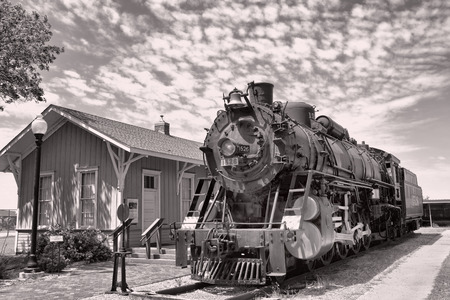 Old railroad steam engine by train station.