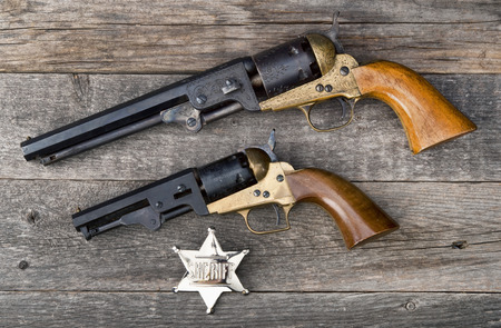 six shooter: The guns that won the west and silver sheriff badge.
