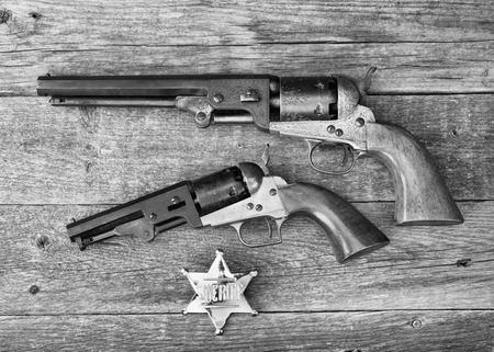six shooter: The guns that won the west and  sheriff badge in black and white.