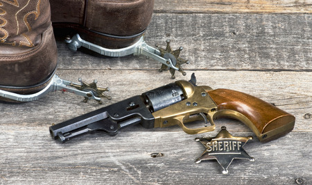 Old western pistol, badge, spurs and cowboy boots.