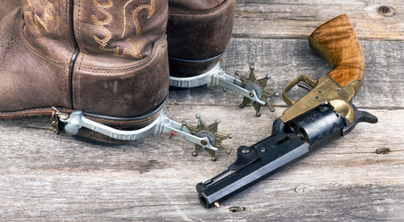 six shooter: Old western pistol and cowboy boots.