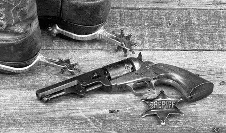 peacemaker: Old western pistol, badge, spurs and cowboy boots in black and white.