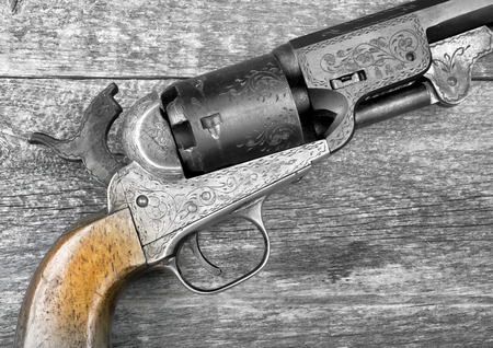 Close up of a western six shooter pistol in black and white.