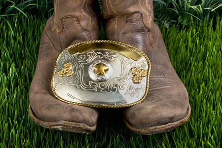 American cowboy with his boots and big silver cowboy belt buckle.