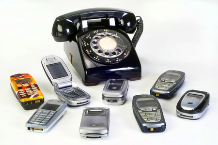 Old working cell phones and black rotary telephone.
