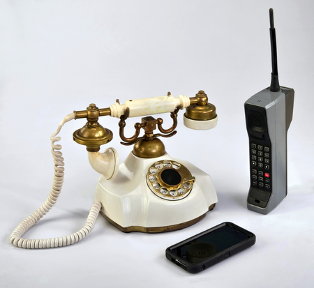 dialplate: Working smart cell phone and old white rotary telephone.