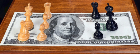 standoff: Chess pieces on American hundred dollar bill. Stock Photo