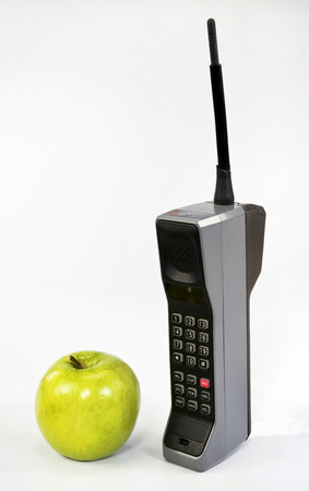 cell phone: Green apple and old brick style cell phone.