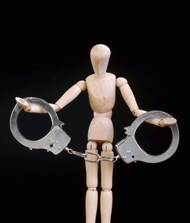 Wooden manikin arrested in handcuffs.