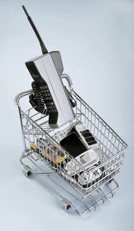 Shopping basket full of old cell phones.